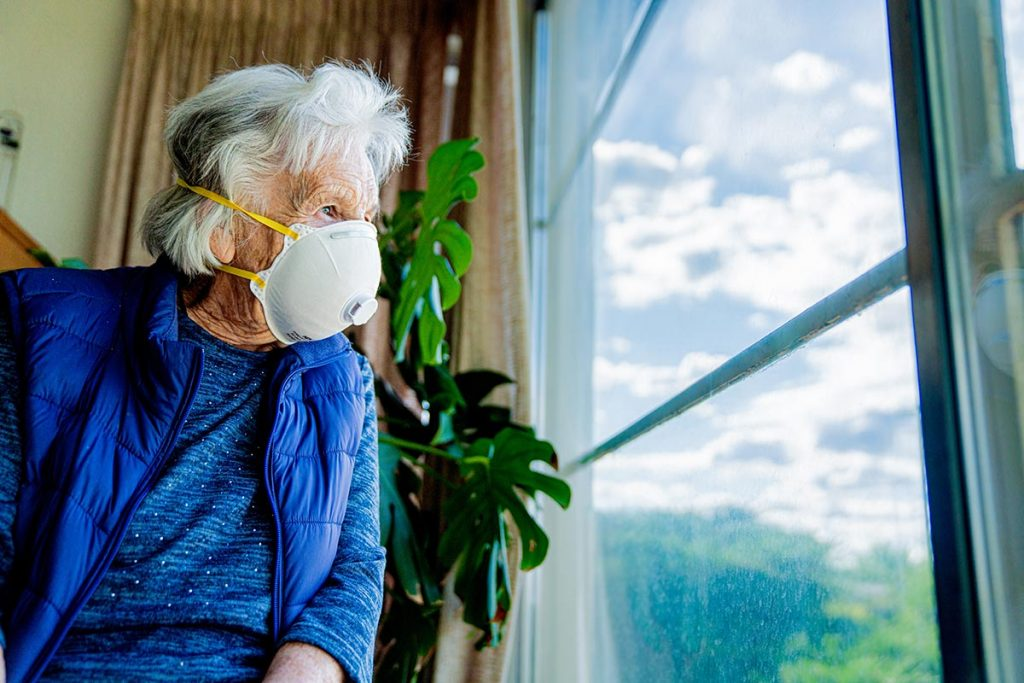 An older adult wearing a face masks peers out a window showing how COVID-19 has isolated older adults.