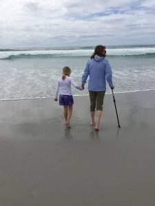 Amy walks on the beach with Sienna, aided by a cane. Lupus symptoms can make walking difficult.
