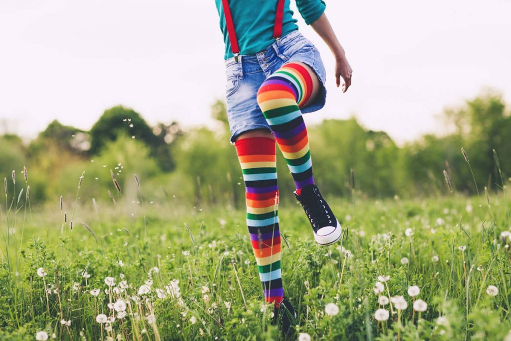 A woman in colorful socks steps through a field of flowers