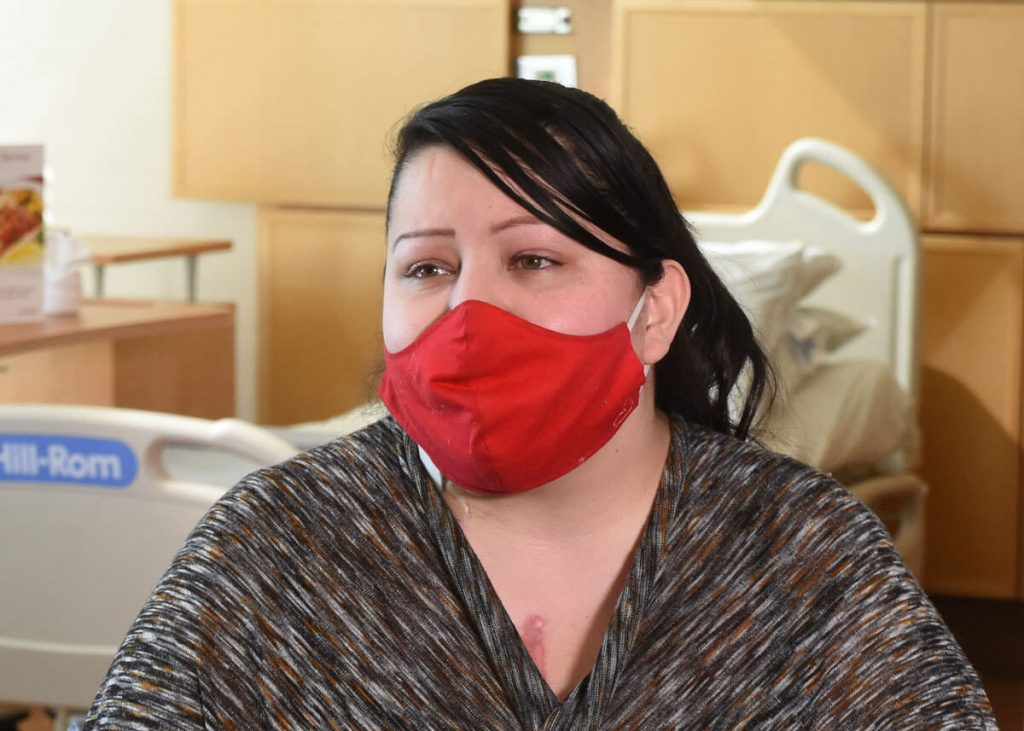woman who had a heart transplant talks about the hospital wayfinding app feature while wearing a red mask.