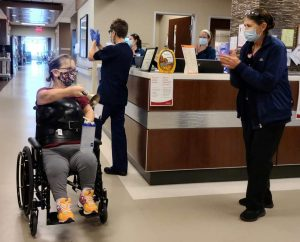 Care givers cheer for Barb Kotzian, who was born with dwarfism, as she rounds a corner at UCHealth Broomfield Hospital after rehab following her spine surgery.