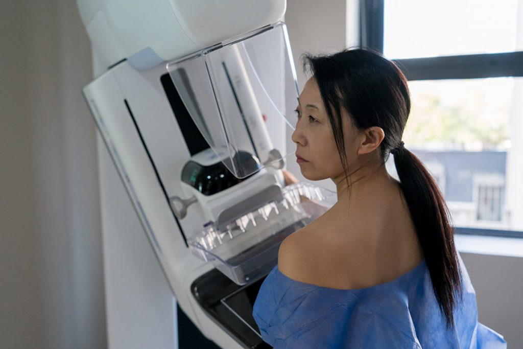 A woman prepares to get a mammogram, which if possible, should be done before getting the COVID-19 vaccine or several months after.