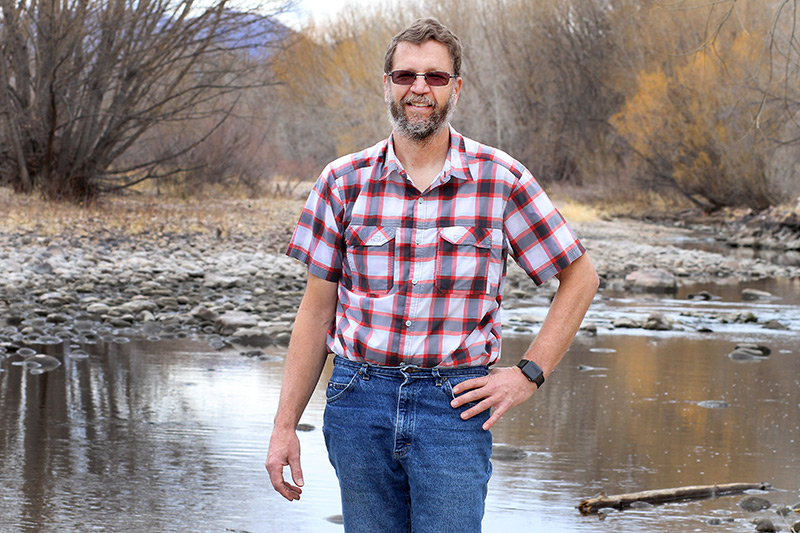 Wade L Clements, who benefited from occupational health services that UCHealth provides employers, stands in front of a river.