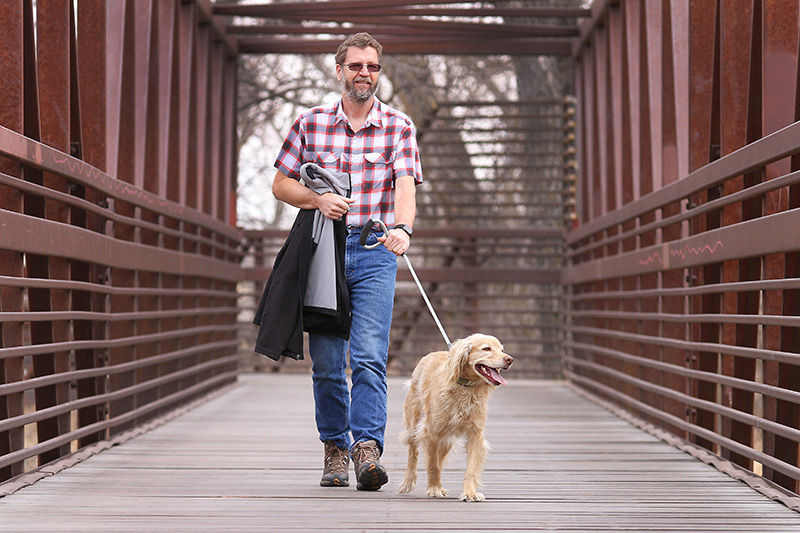 Wade L. Clements enjoys a walk with his dog Diesel. Because his employer partners with UCHealth for occupational health services, Wade's heart murmur was found before something serious happened to him.
