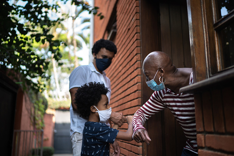 What's safe after vaccine? Here, a grandmother wearing a mask greets her grandson.