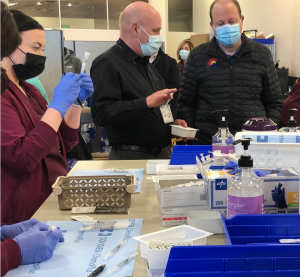 Larry Tremel, UCHealth's pharmacy director in southern Colorado, talks to Colorado Gov. Jared Polis as pharmacy techs prepare COVID-19 vaccinations.