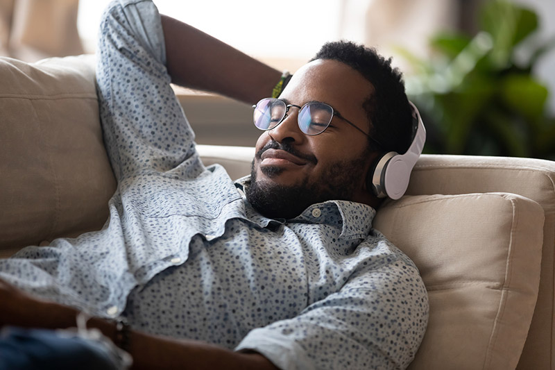 man listening to music while relaxing on the couch can be a great way to benefit from music.