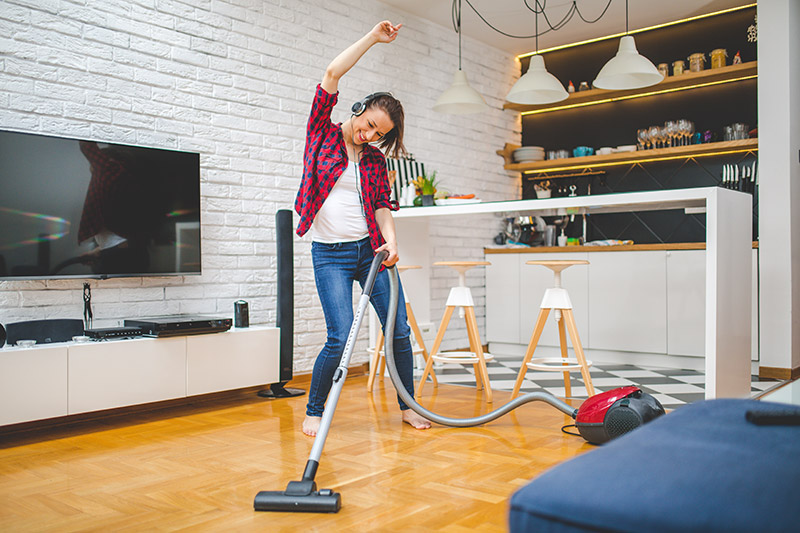 woman dancing while cleaning, a great benefit of music is that it can help motivate you to do what you want to do.
