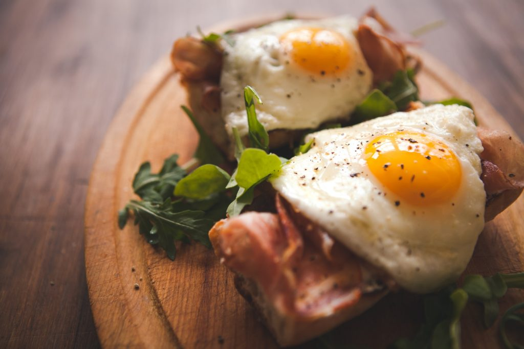 Here, we see fried eggs on a baguette with ham for this article about how to cook eggs.