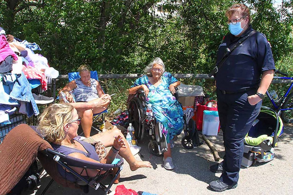 UCHealth community paramedic Julie Bower talks with a homeless family in Fort Collins.