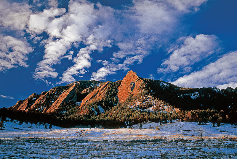 Coloradans are reeling after the Boulder mass shooting at a grocery store. This photo shows Boulder's iconic red Flatirons with snow and blue sky. Photo: Getty Images.