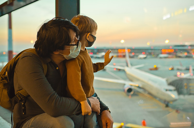 boy and father wearing masks looking out at plane at an airport before they travel during a pandemic.