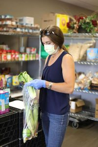 Laura Elliot, the Food Pantry's coordinator, gathers produce for an FMC Food Pantry client. Perhaps the biggest change the coronavirus pandemic introduced was that Food Pantry staff and volunteers fulfill orders for clients.