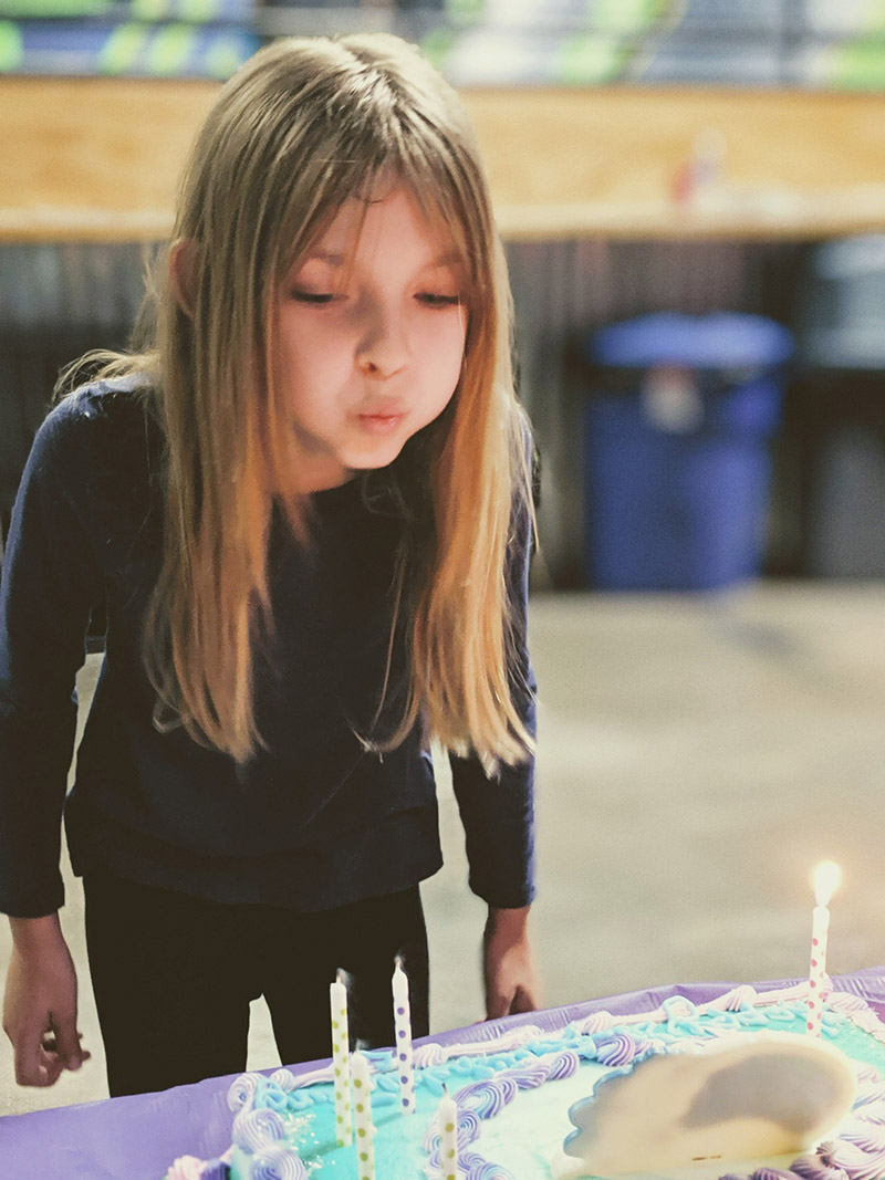 Juno blowing out the candles of her 8th birthday cake.