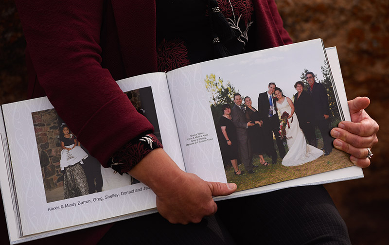 Losing family members to COVID-19 is devastating. Dr. Michelle Barron holds her wedding album. She's posing with her cousins and a beloved aunt and uncle who died of COVID-19.