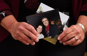 Dr. Michelle Barron holds a photo from her wedding when she posed with her Uncle Rick, who has since died of COVID-19.