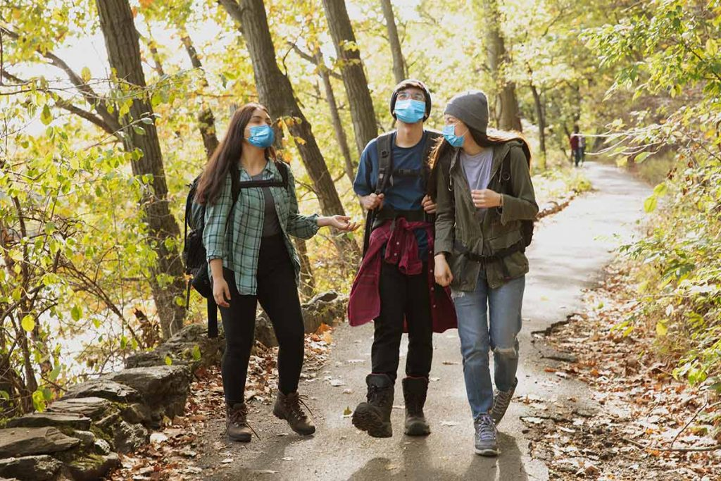 Three teens hike while wearing masks. CDC recently released new guidelines for wearing masks outdoors.