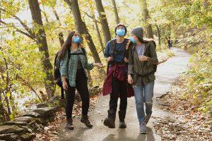 Three teens hike while wearing masks