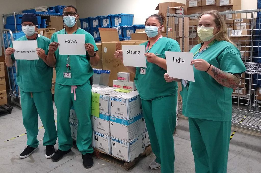 A photo of four health care workers holding up signs supporting the effort to send medical supplies to India.