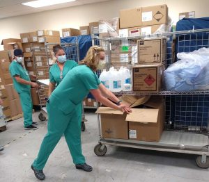 UCHealth's Shauna Sutton, associate operating room nurse manager, helps move donated medical supplies bound for India. Photo by UCHealth