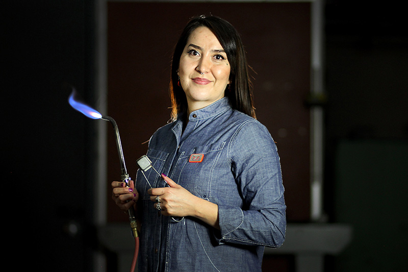 Priscilla Gonzalez holding a metalsmith torch. Her art demonstrates her efforts for colon cancer awareness.
