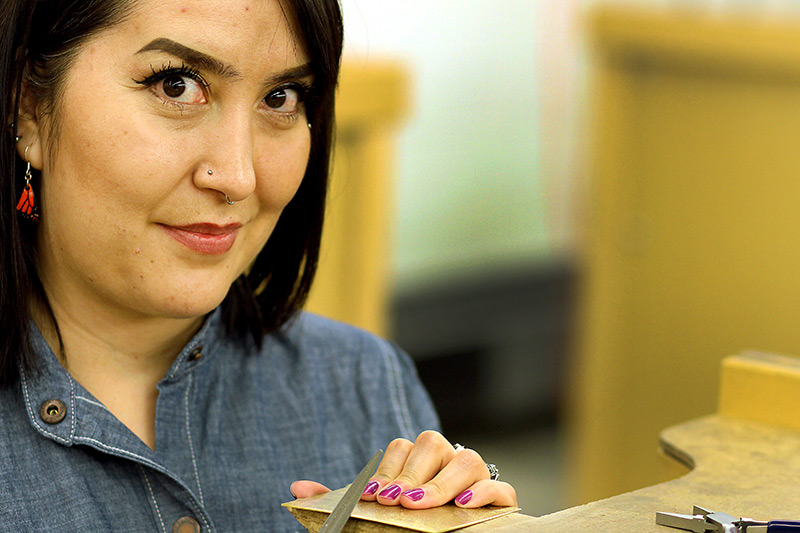 Priscilla Gonzalez doing metalsmithing. Her art demonstrates her efforts for colon cancer awareness.