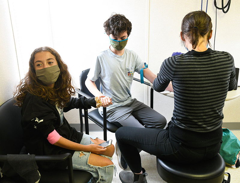 kids clinical trials for COVID-19 vaccines. Emilia Vannoni, 12, left, holds her twin brother's hand as he gets blood taken.