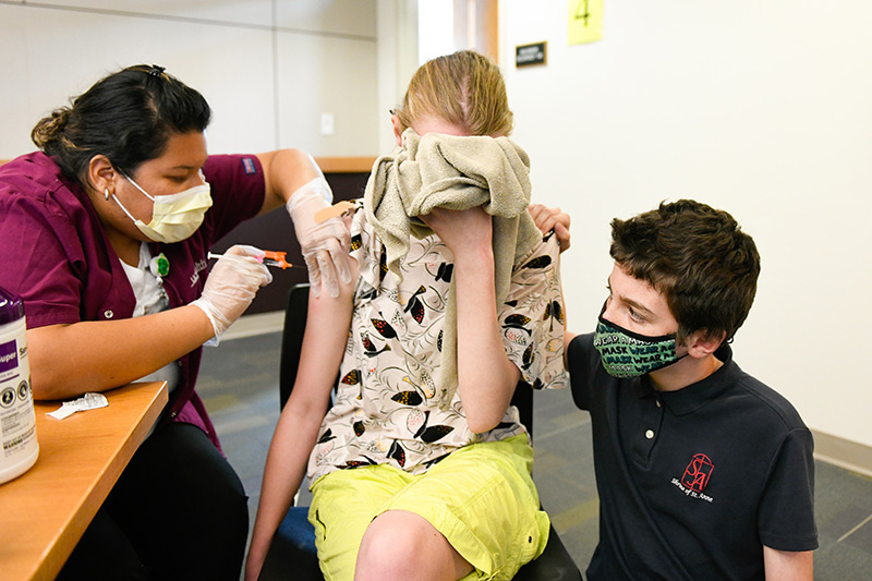 kids start getting their COVID-19 vaccines. Meghan Williams covers her face with the blankie she had when she was a baby as her brother, Wilson, 10, comforts her.