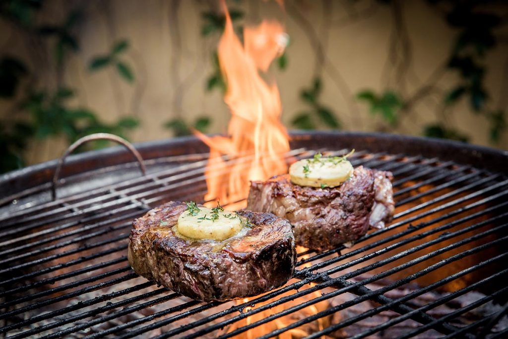 A photo of two grilled flat iron steaks sizzling on an outdoor grill.
