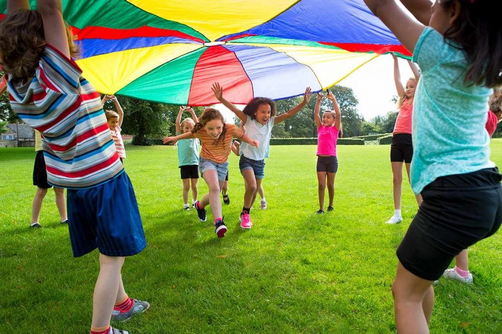 Kids playing under a canopy in a park with green grass as part of safe party planning ideas.