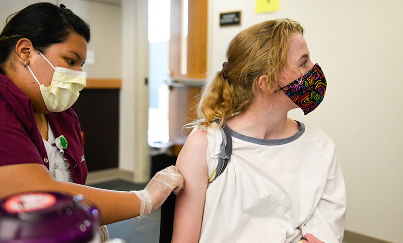 Kate Williams turns away as she receives a vaccine at UCHealth University of Colorado Hospital.