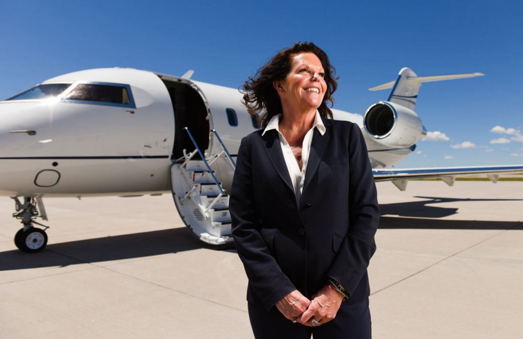 Gail Sadler, a lung cancer patient, on the tarmac outside Modern Aviation where she works at Centennial Airport.