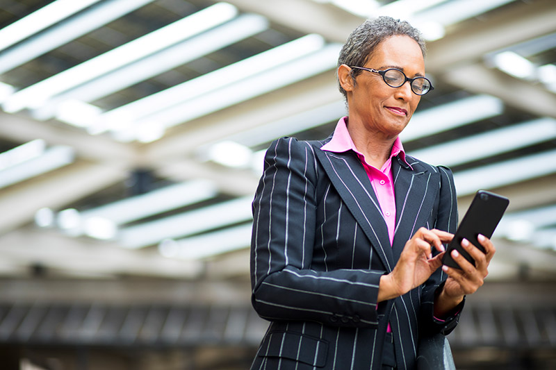 business woman looks to her phone to verify vaccination records while traveling.