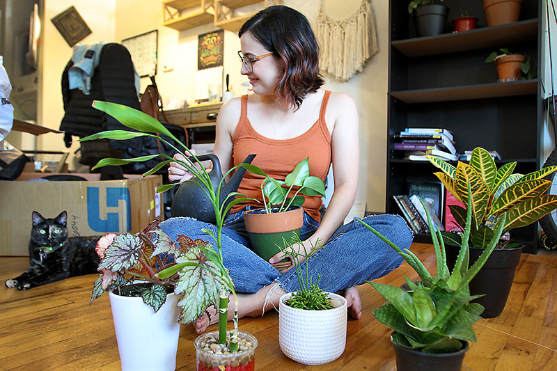 Audrey Lopez, with help from her cat, Calla, waters her plants at her Fort Collins, Colorado, apartment recently. Lopez was in the process of moving to a place that's more accessible for her to get around with her cane. Photo by Joel Blocker, for UCHealth.