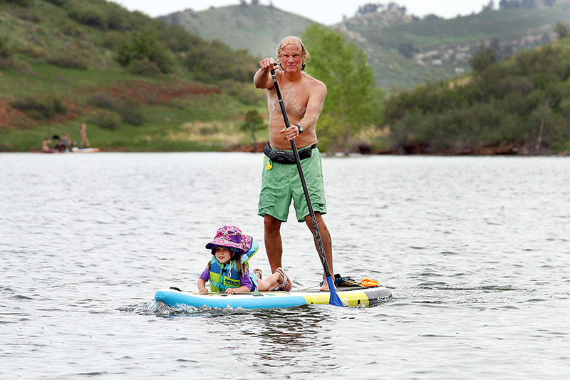 Rick Felton and his granddaughter, Avery, enjoy an afternoon paddleboarding at Horsetooth Reservoir west of Fort Collins, Colorado. Photo by Joel Blocker, for UCHealth.