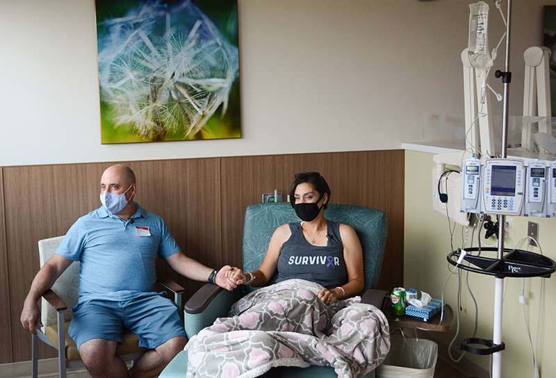 Cathy and Tony Pane hold hands as she receives her final infusion treatment at UCHealth Highlands Ranch Hospital.