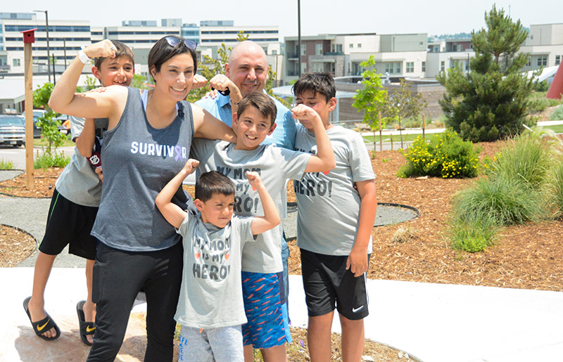 Cathy Pane poses with her husband and four sons after finishing her last chemotherapy treatment for small bowel cancer at UCHealth Highlands Ranch Hospital.