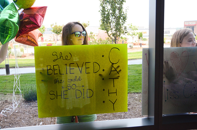 A friend holds a poster outside UCHealth Highlands Ranch Hospital as Cathy Pane finishes her final infusion treatment.