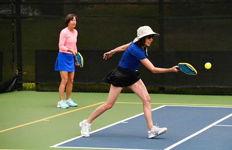 What is pickleball? Two women who are learning to play pickleball play on a court at Gates Tennis Center in Denver.
