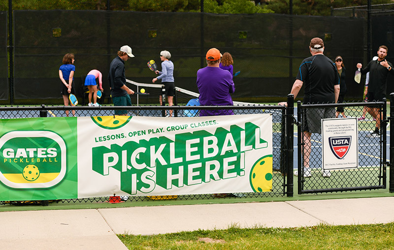 """What is pickleball. A banner at Gates Tennis Center reads """"pickleball is here."""""""