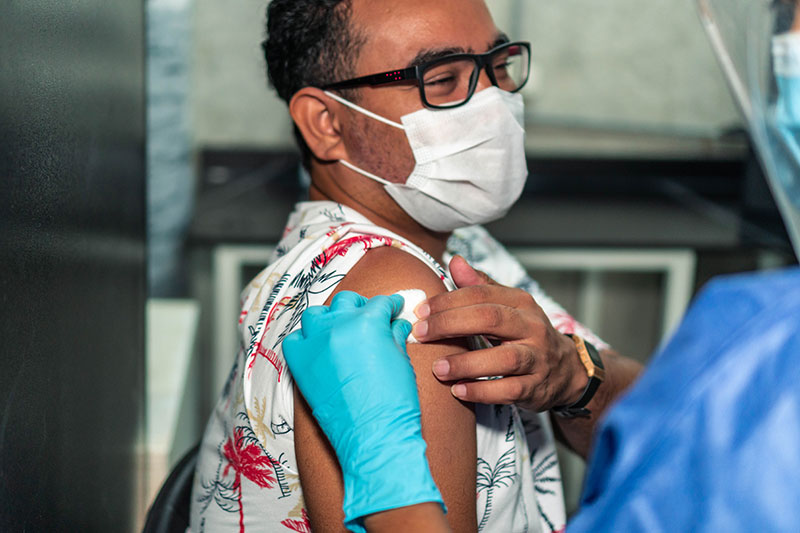 man with autoimmune disease getting a COVID-19 vaccine