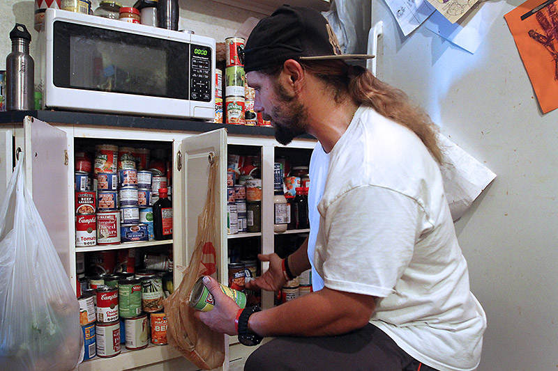 Les Johnson picks out canned goods, which he got at FMC food pantry, in preparation of dinner. Photo by Joel Blocker, for UCHealth.