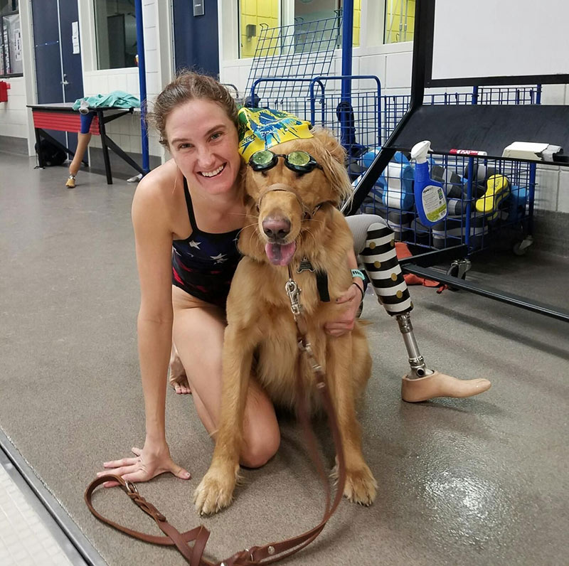 Paralympian Allysa Seely on the deck of the pool poses with her service dog, Mowgli.
