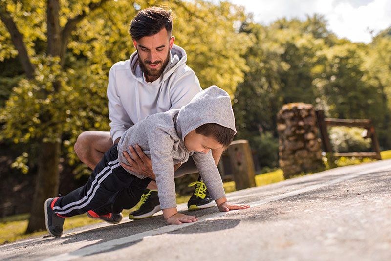 dad helping his young athlete do a pushup