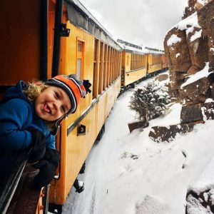 child holds his head out a train car on a scenic train ride in Colorado