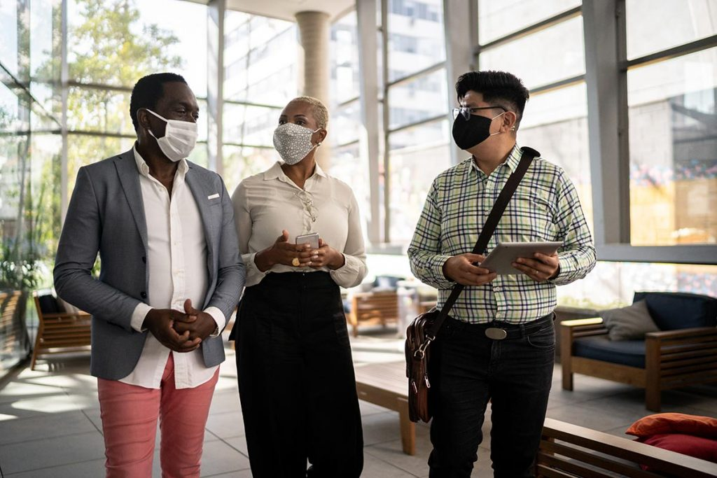 Photo of professionals talking in a lobby of an office building