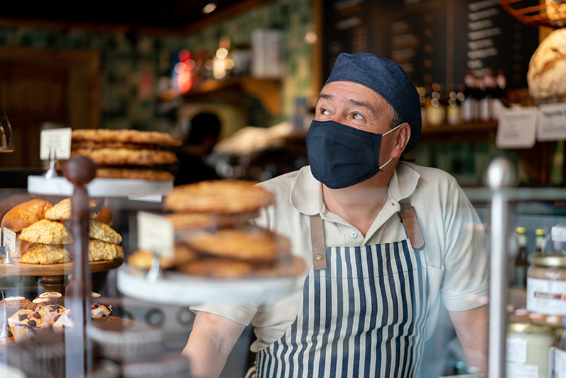 The delta variant and vaccines. A man working at a cafe wears a mask.