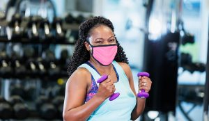 The delta variant and masks. Should you wear a mask indoors again? Here a woman wearing a mask works out in a gym.