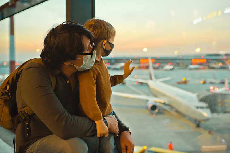 The delta variant and masks. A father and son wear masks at an airport.