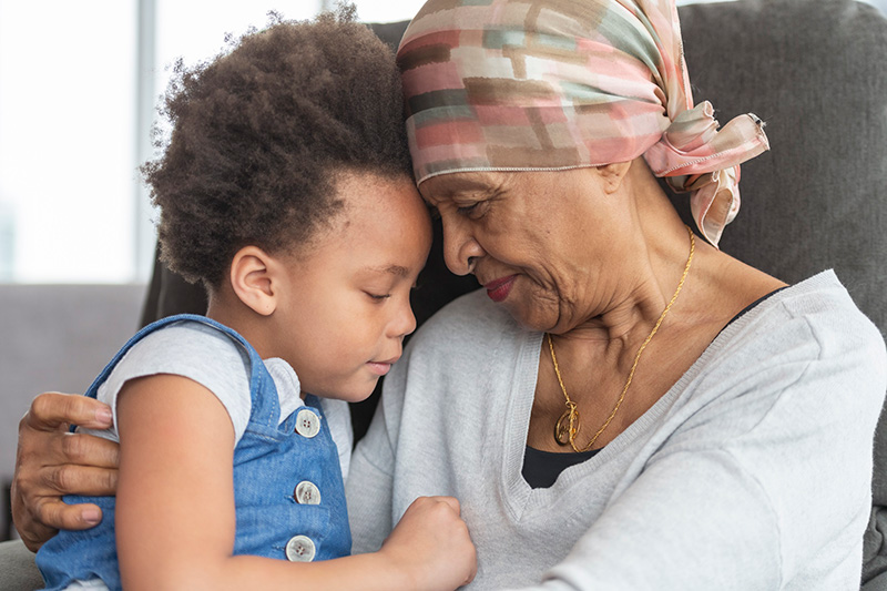 Booster shots for immunocompromised may help prevent breakthrough COVID-19 cases. An older cancer patient holds her granddaughter.